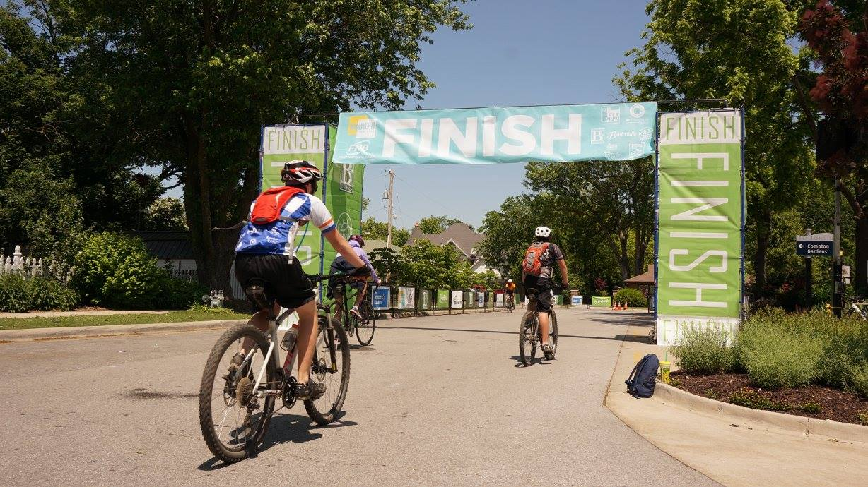 Three adults riding bicycles down a city street across a finish line