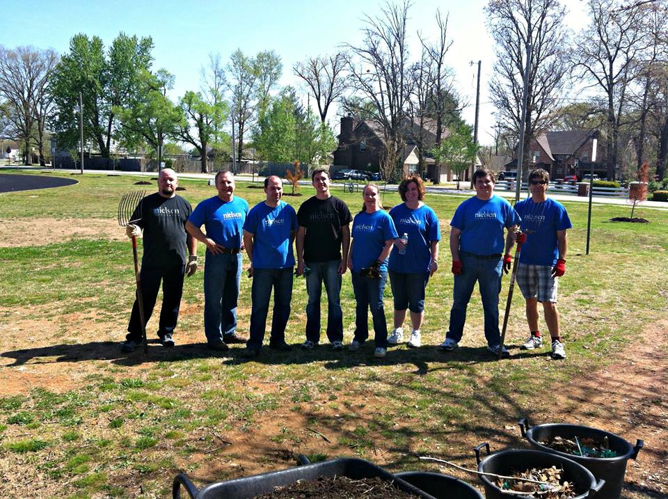 Eight people in blue volunteer shirts standing together with gardening tools on lawn