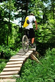 Slaughter Pen Mountain Bike Trail Image of biker on wooden trail