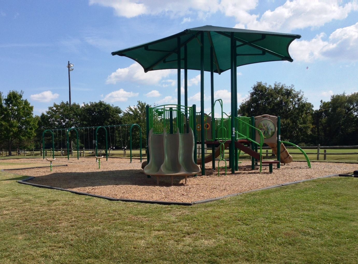 Phillips Park Image of Playground in grass with trees in balcground