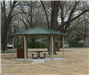 Gilmore Park Pavilion in treed park with picnic table